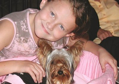 Yorkie Yorkshire Terrier cuddling with little girl